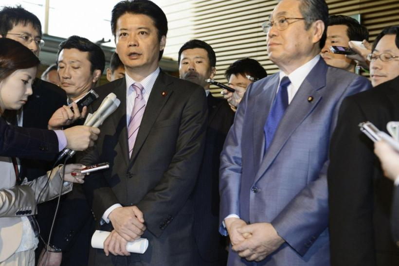 Japan's Foreign Minister Gemba, flanked by Defence Minister Tanaka, is surrounded by reporters in To