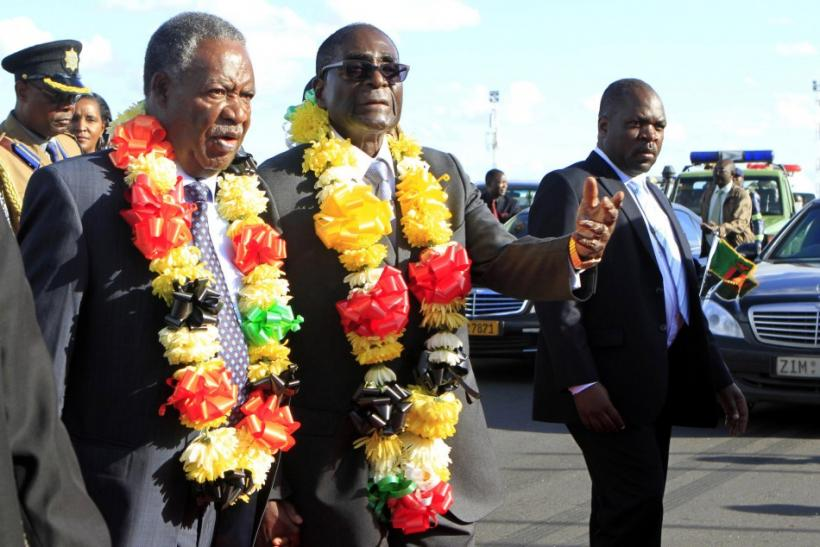 Zimbabwe President Robert Mugabe walks with Zambian President Michael Sata as he arrives for the Zimbabwe International Trade Fair (ZITF)