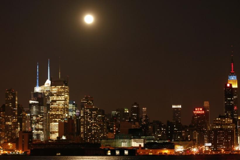 A full moon rises above the skyscrapers in Times Square and the Empire State Building in New York