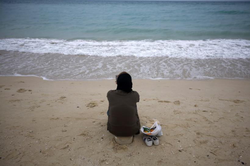 Iranian woman sits on southern beach on island of Kish in Persian Gulf 1250 km south of Tehran