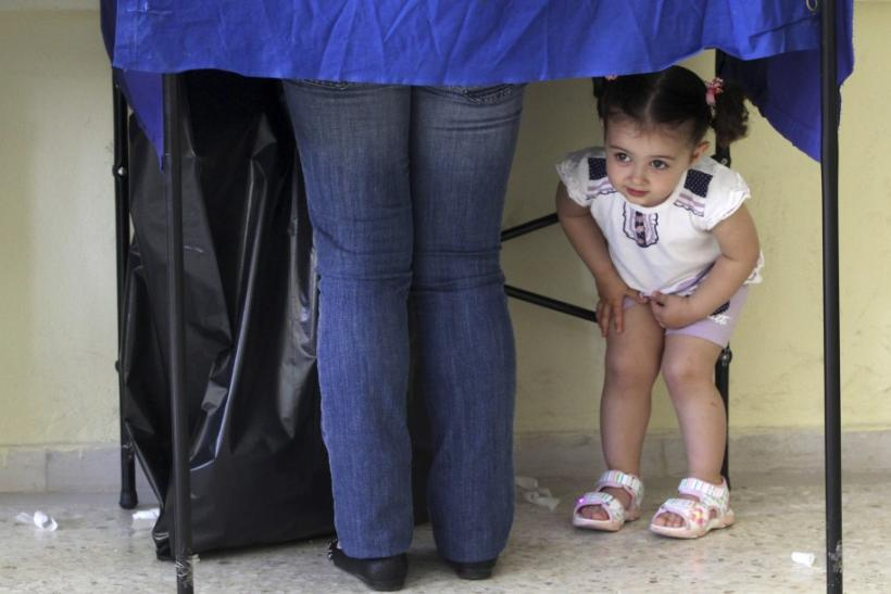 A girl peers under a polling booth during Greek elections in Athens