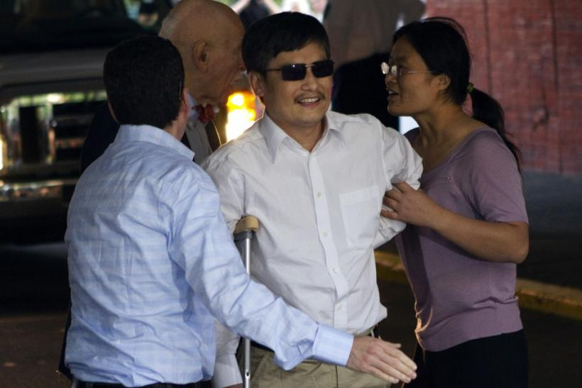 Blind Chinese dissident Chen Guangcheng (C) is helped by his wife Yuan Weijing (R) after arriving in New York May 19, 2012.