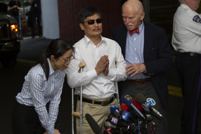 Blind Chinese dissident Chen Guangcheng (C) speaks to members of the media after arriving in New York