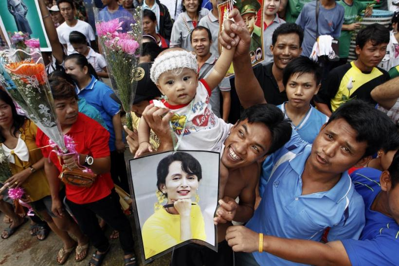 Migrant workers from Myanmar hold a picture of pro-democracy leader Suu Kyi and flowers in Samut Sakhon province