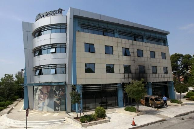A security guard stands outside Microsoft's Greek headquarters following an attack at Marousi suburb, north of Athens.