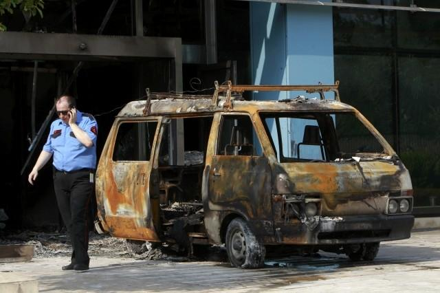A security guard speaks on the phone following an attack on Microsoft's Greek headquarters at Marousi suburb, north of Athens.