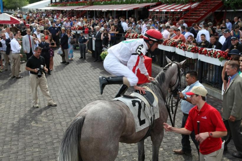 A jockey dismounts in the winner's circle at the Saratoga Race Course opening weekend.