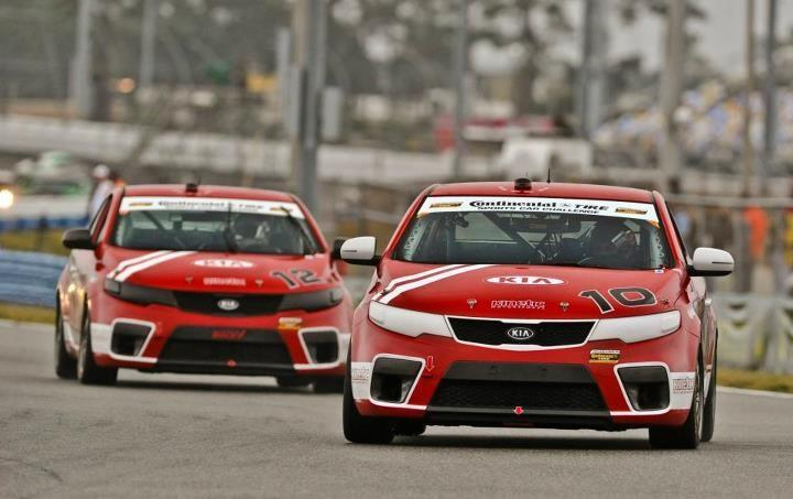 Two of Kia's Forte Koup racecars piloted by Kinetic Motorsports on the track.