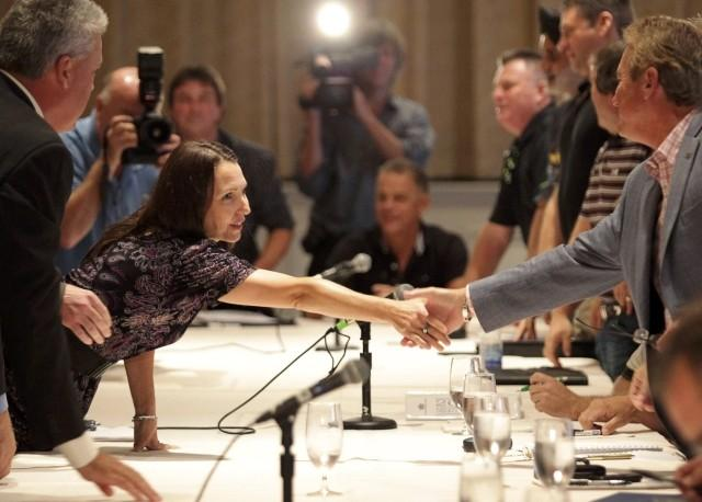 Oliva, Chrysler Canada's Labour Relations representative, shakes hands with Kennedy, CAW national secretary treasurer, while CAW representatives prepare to discuss contract negotiations with Chrysler Canada representatives, in Toronto
