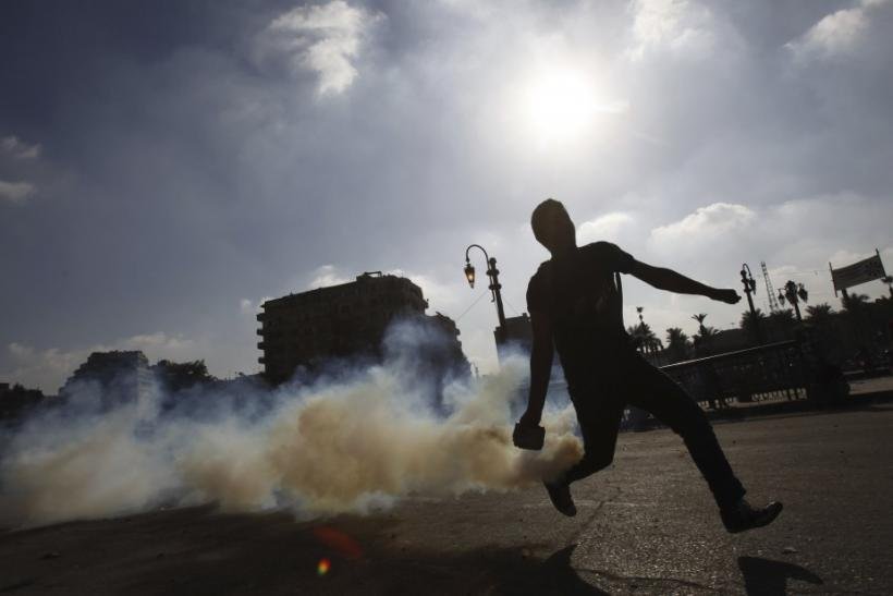 A protester throws a tear gas canister, which was earlier thrown by riot police, during clashes along a road which leads to the U.S. embassy, in Cairo
