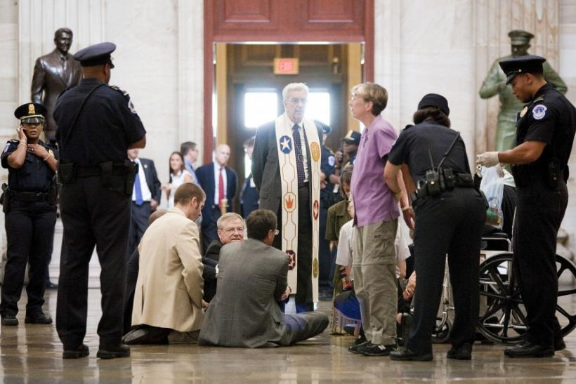Reverend Paul Sherry and other religious leaders take part in a protest, calling on Congress to reach a budget agreement that protects the nation's most vulnerable, refuse to comply with an order from Capitol police to clear the Rotunda in Washington