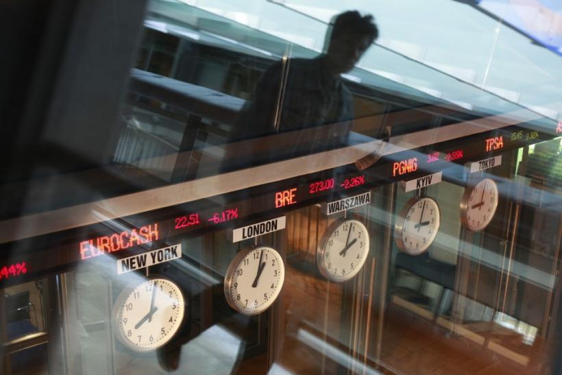 A man reflects in a window as he passes near clocks at the Warsaw Stock Exchange