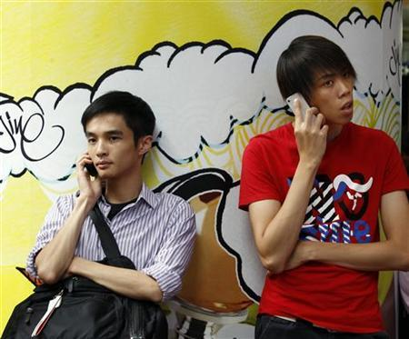 Two men use mobile phones as they wait outside a department store in Hong Kong
