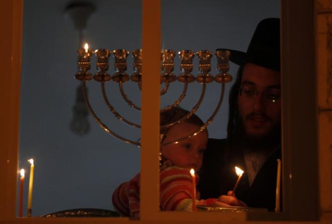 208881-an-ultra-orthodox-jewish-man-holds-a-child-as-he-lights-a-candle-for-h