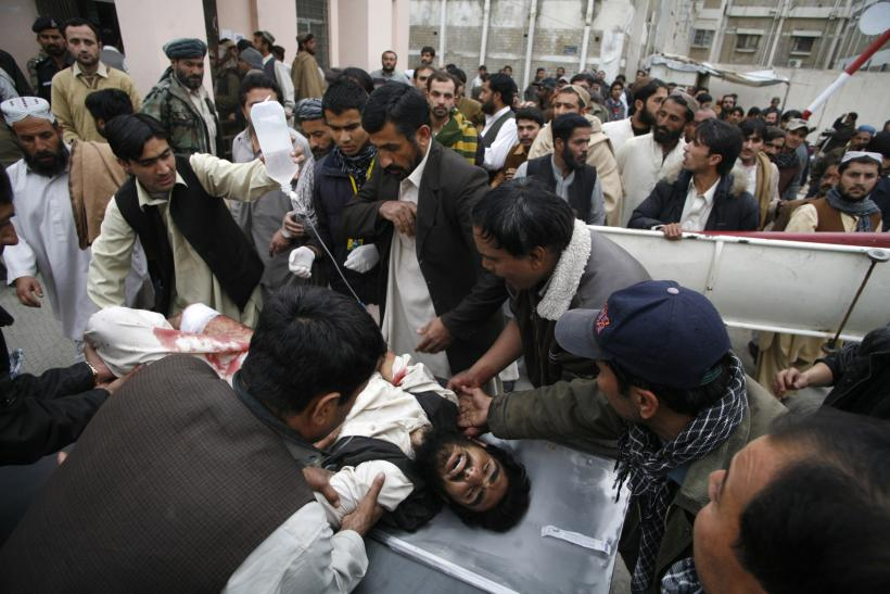 People wheel a man who was injured by a bomb explosion, at a hospital in Quetta