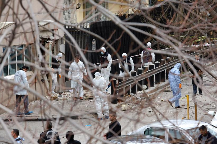 Turkish police forensic experts inspect the site after an explosion at the entrance of the U.S. embassy in Ankara February 1, 2013.