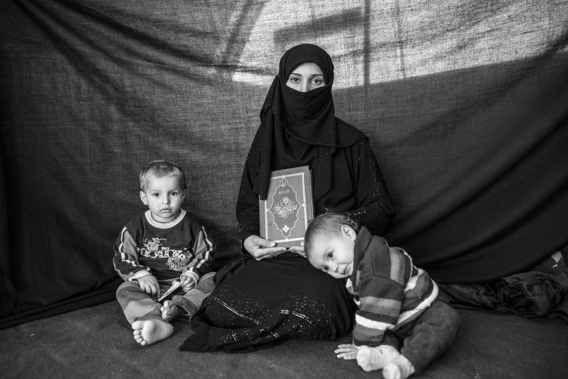 Syrian Refugee Mother With Her Children And Koran