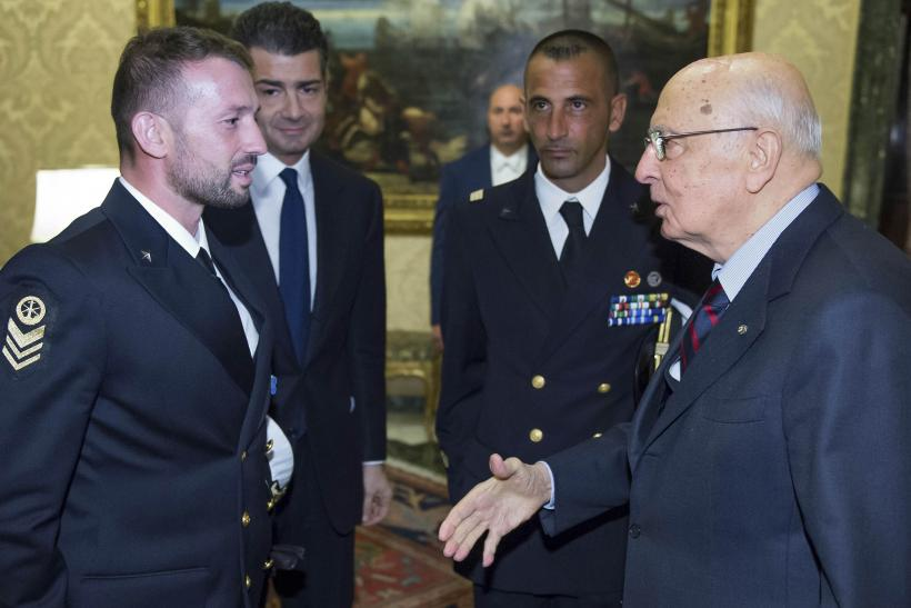 Italian President Giorgio Napolitano (R) greets two Italian marines Salvatore Girone (L) and Massimiliano Latorre (2nd R) during a meeting at Quirinale presidential palace in Rome, December 22, 2012.