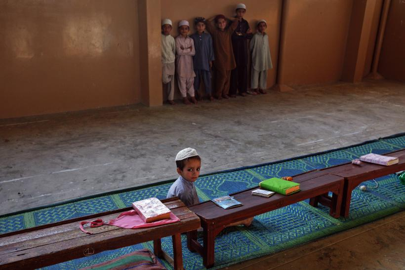 A student sits on floor while others stand beside a wall in a madresa (religious school) on the outskirts of Karachi
