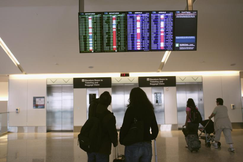Airline passengers look at a flight status board at San Francisco International Airport in San Francisco