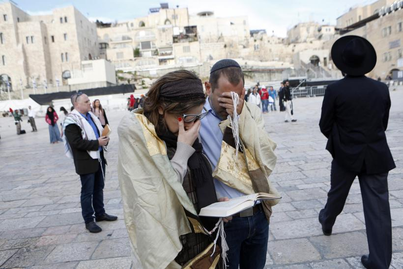 Woman and man praying at Western Wall