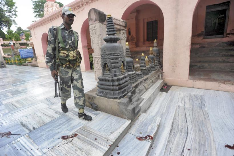 An Indian security personnel walks next to bloody footprints inside the Mahabodhi temple complex, after a series of explosions at Bodh Gaya