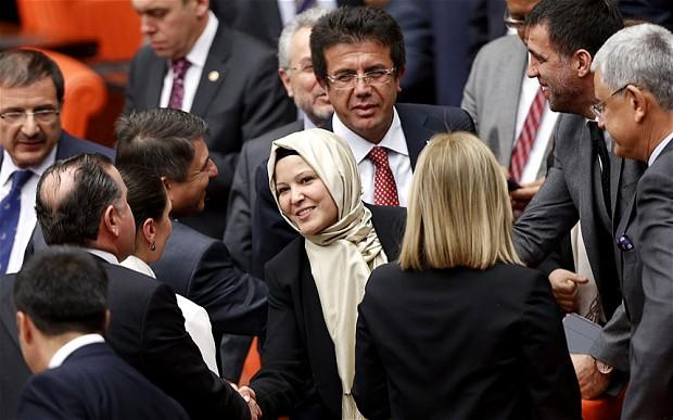 Turkey's ruling AKP politician Nurcan Dalbudak is congratulated by her party's lawmakers as she attends the general assembly wearing her headscarf at the Turkish Parliament in Ankara