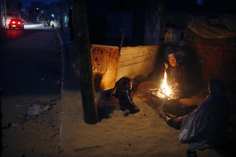 A Palestinian family warm themselves by a fire outside their house during a power cut in the northern Gaza Strip November 17, 2013