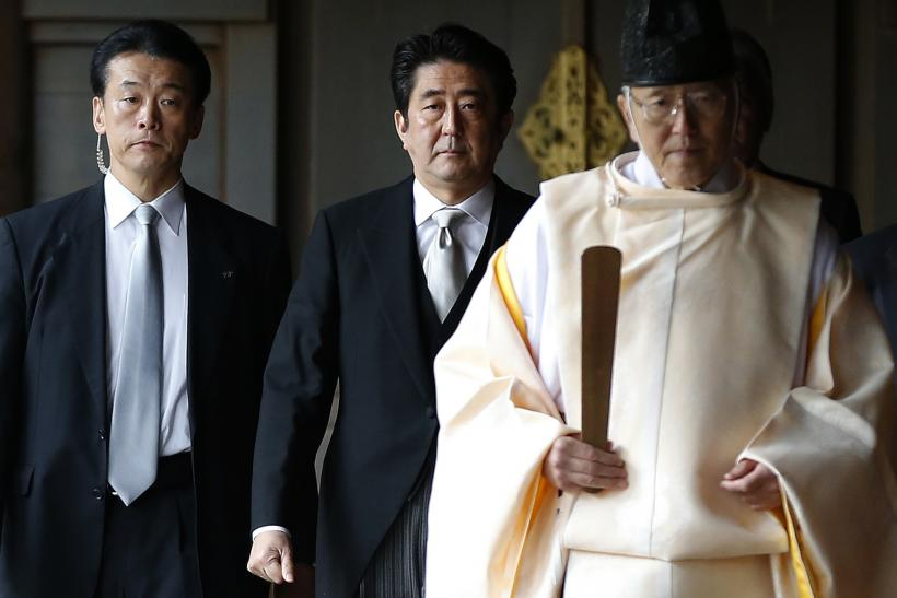Japan's Prime Minister Shinzo Abe (C) is led by a Shinto priest as he visits Yasukuni shrine