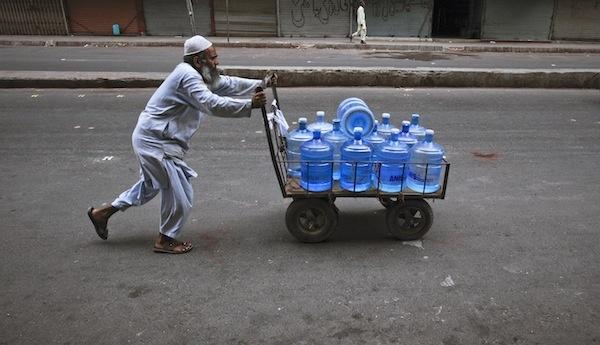 Pakistani man transporting bottled water