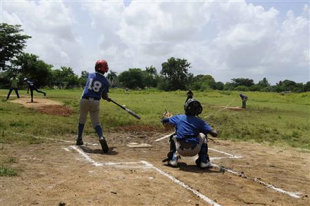 Dominican boys practice baseball at a park in Guerra August 10, 2013.