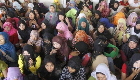 Indonesian workers ready to fly to Saudi Arabia to work as maids wait at a shelter during a police inspection in