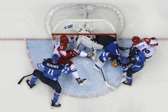 Russia's Alexander Radulov (47) tries to push the puck into the goal as Finland's goalie Tuukka Rask (3rd R) defends during the third period of their men's quarter-finals ice hockey game at the Sochi 2014 Winter Olympic Games February 19, 2014.