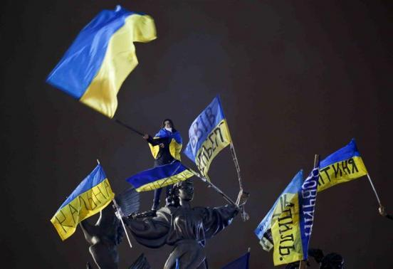 A Pro-European integration protester waves a Ukrainian national flag as she stands on a statue during a mass rally at Independence Square in Kiev