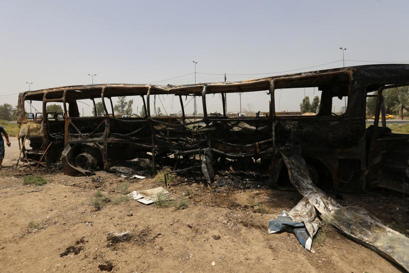 A man walks past a burnt bus in Taji, north of Baghdad July 24, 2014