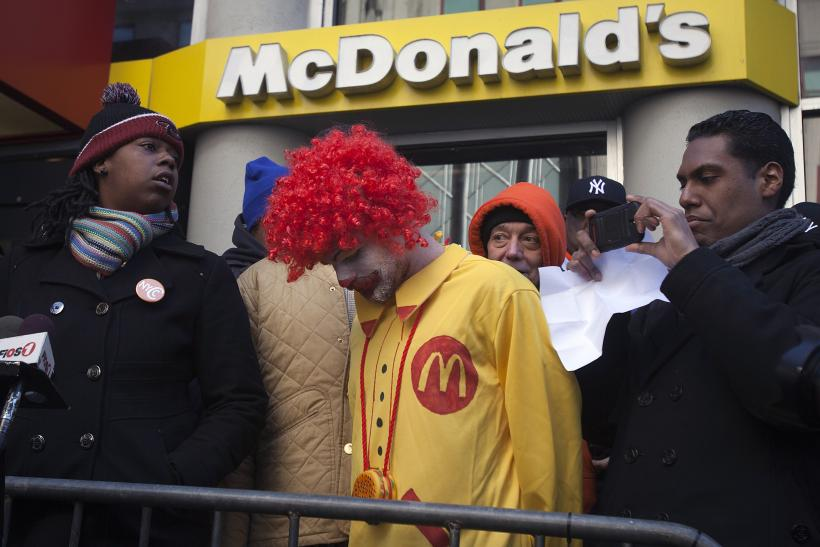 A protester Ben dressed up as Ronald McDonald, only known as Ben, takes part in a protest outside a McDonalds restaurant to demand higher wages for fast food workers in the Manhattan borough of New York March 18, 2014