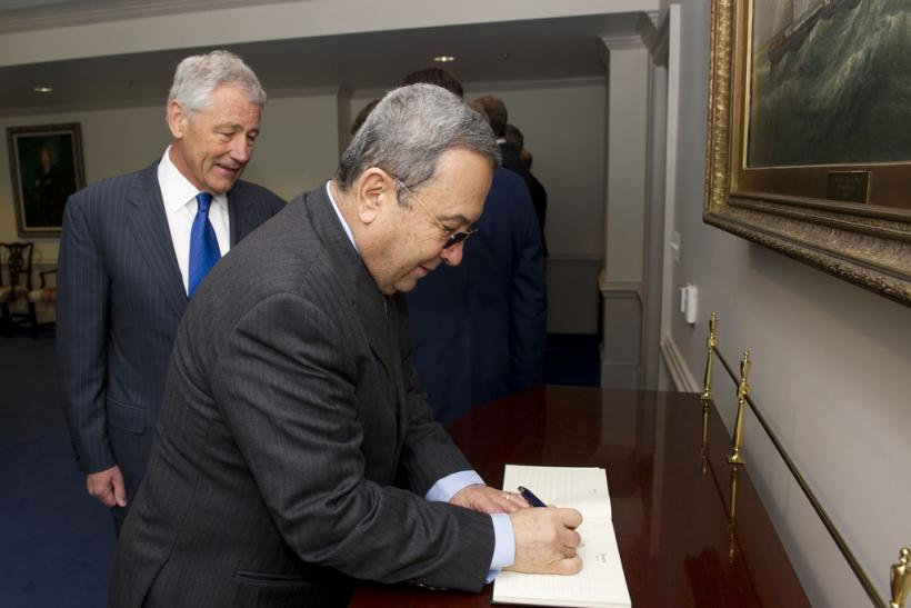 Barak signs the guest book at the Pentagon with Hagel