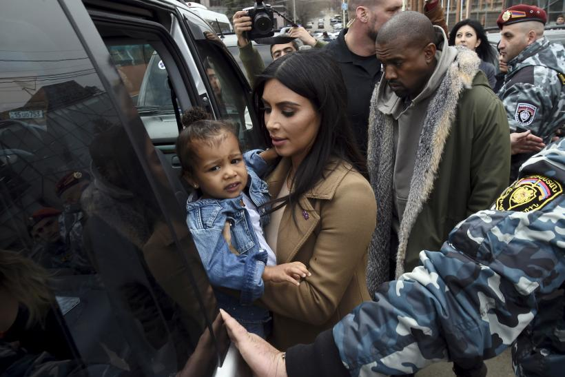[11:10] U.S. television personality Kim Kardashian together with her rapper husband Kanye West (R) and their daughter North, gets into a car during their visit to Yot Verk Church